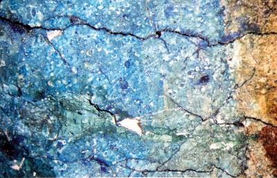 Mikroskopisches Detail der Bildschicht im Bereich der Schulter der mittleren Figur: Zu sehen sind dunkel die Craquelésprünge, entlang derer kleine Malschichtpartikel bereits fehlen oder durch Abheben vom Verlust bedroht sind.