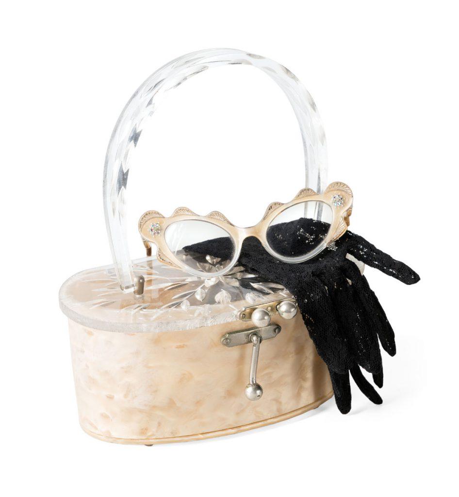 Arrangement aus Handtasche aus Kunststoff mit Henkelhalterung und Verschluss aus Metall, Brille aus Kunststoff mit Wellenverzierungen und Strasssteinen sowie Netzhandschuhen aus Perlon, 1956–1958; © Modemuseum Schloss Meyenburg e.V. / Foto: Ulrich Lange, Dessau, vierzig-a.de