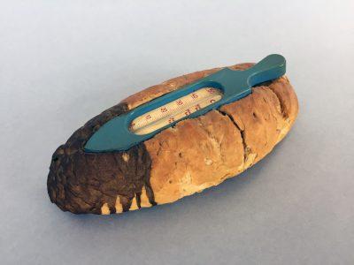 Wolf Vostell, Prager Brot, 1968, 1/2 kg Weizenbrot mit eingelassenem Badethermo-meter, teilweise mit Gold übergossen, 25 × 11 × 8,5 cm, VICE-Versand, Remscheid; Sammlung / Archiv Andersch; © Foto: Bernd Trasberger