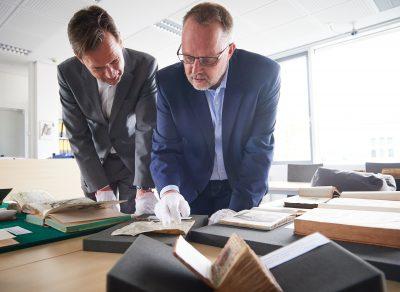 Direktor der ULB, Herr Dr. Meyer-Doerpinghaus (links) und der Dezernent für Handschriften und Altbestand, Herr Dr. Herkenhoff (rechts) mit in den Bestand der ULB zurückgeführten Werken © Volker Lannert/Uni-Bonn