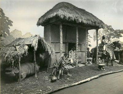 Die Schlitztrommel aus Bafu-Fondong (unter dem überdachten Verschlag im linken Bildabschnitt) in einem Bamum-Diorama auf der Kolonialausstellung in Stuttgart 1928. Foto: Unbekannt (LiMu Ausstellungen 1928)